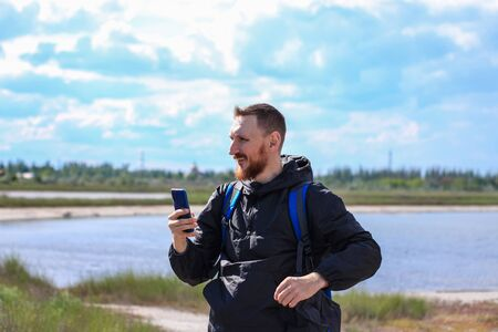 Bearded smiling man in black raincoat on blue sea landscape background with smartphone in hands takes seascape photography. Running young hipster guy portrait with cell phone, lifestyle nature photo.