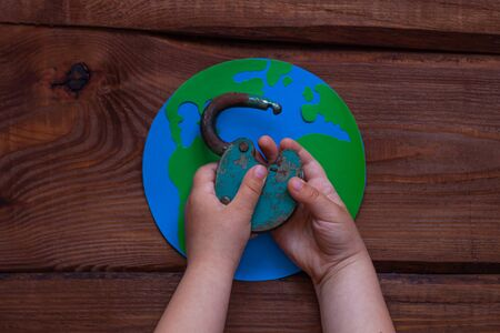 Lockdown is over creative concept, open iron lock in child's hands on wooden background. Opening borders between countries. End of Quarantine COVID19, back to normal life.Social media coronavirus news