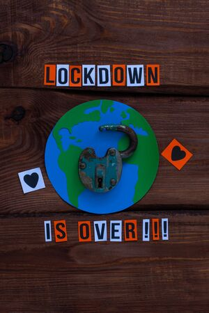 Lockdown is over sign, planet Earth, open lock on wooden background. Opening borders between countries. End of Quarantine COVID-19 concept creative flat lay, back to normal life.Media coronavirus news