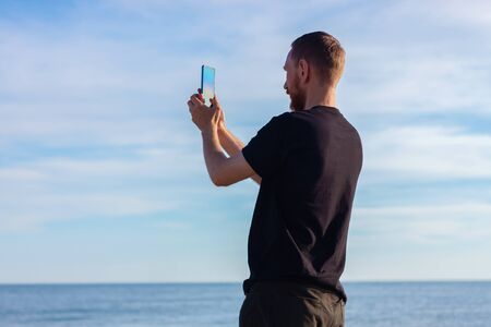 Bearded man in black t-shirt on a sea and clear blue sky landscape background with smartphone in hands taking a picture. Young guy photographing nature on cell phone, active lifestyle travel concept. Archivio Fotografico