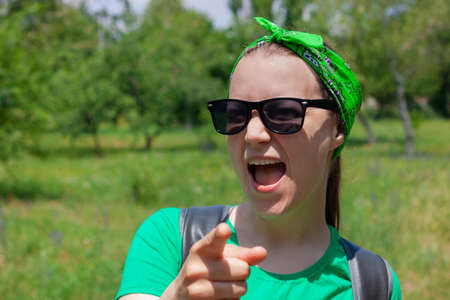 Portrait of a pretty hipster girl in sunglasses, green shirt, bandana standing on nature background on sunny day.Positive emotional caucasian young lady smiles, shows a finger and looks at the camera.