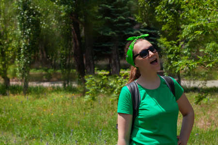 Portrait of a pretty hipster girl in a sunglasses, green shirt and bandana standing on a nature background on sunny day. Positive emotional caucasian young long haired lady smiles and looks on the sky Stok Fotoğraf