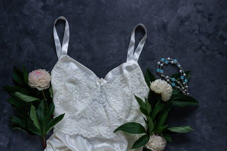 Woman's glamour white lingerie and jewelry accessories with peony flowers on dark background. Female fashion blog flat lay social media copy space. Lace underwear combine sexy, silk clothes top view. Stockfoto