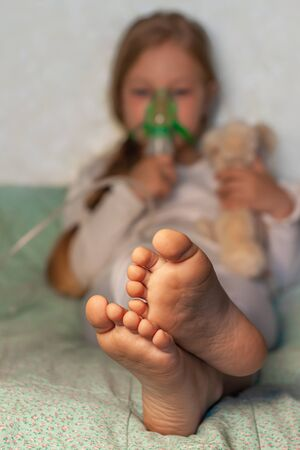 Little girl making inhalation with nebulizer on a bed at home. Sick allergic kid asthma inhaler steam cough. Child allergy concept.Respiratory diseases lungs medicine treatment.Selective focus on feet