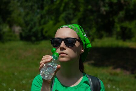 Young girl holds a bottle of water in hand and drinks. Portrait of pretty hipster in sunglasses, green shirt, bandana stands on the nature on sunny day. Weight loss, summer active lifestyle body care.
