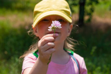 Positive emotional young lady smiles, looks on wild flower that holds in hand. Cheerful pretty child girl in yellow baseball cap, pink shirt, stands on nature background on sunny day. Happy childhood.