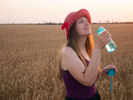 Young girl in hat holds a bottle of water in hand and drinks water in wheat field. Weight loss, summer active lifestyle body care. Rehydration body in hot weather,human organism liquid assets keeping. Archivio Fotografico