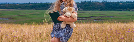 Child girl in a straw hat and dress staying near vintage suitcase and reading a book. Cute kid with soft dog toy looking at notebook in hand nature lanscape background retro style.Header banner design