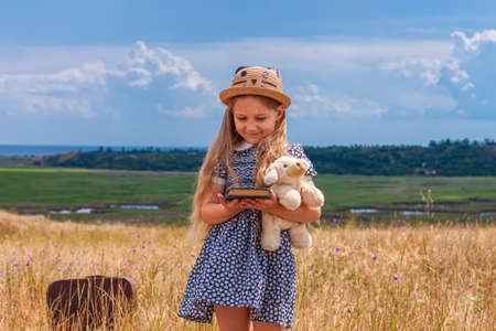 Child girl in a straw hat and dress staying near vintage suitcase and reading a book. Cute kid with soft dog toy looking at notebook in hands nature lanscape background. Adventure concept retro style. 免版税图像