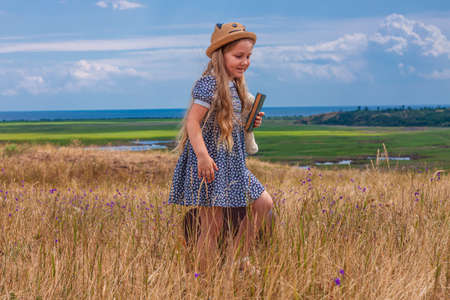 Child girl in a straw hat and dress staying near vintage suitcase and reading a book. Cute kid with soft dog toy looking at notebook in hands nature lanscape background. Adventure concept retro style. Stockfoto