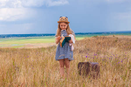 Child girl in a straw hat and dress staying near vintage suitcase and reading a book. Cute kid with soft dog toy looking at notebook in hands nature lanscape background. Adventure concept retro style.