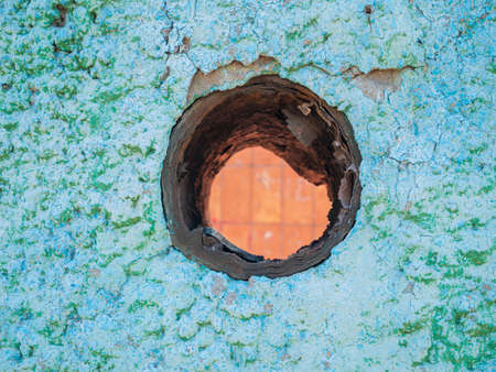 Old turquoise plaster wall texture with hole. Retro painted putty building background with copy space. Stylish blue surface, detailed stones backdrop. Wallpaper textured screensaver front view design. 免版税图像
