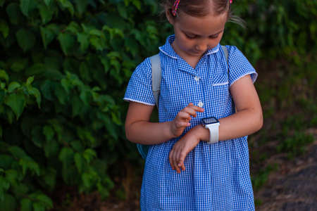 Kid using smartwatch outdoor in park. Child talking on vdeo call on the smartphone. Schoolgirl using touchscreen display on watches browsing internet. Smart wristwatch with GPS tracker.