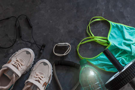 Sports lifestyle flatlay composition, trendy white sneakers, sport watch, aqua turquoise bra, headphones, fitness chest expander, ab wheel abdominal training, water bottle on gray concrete background.