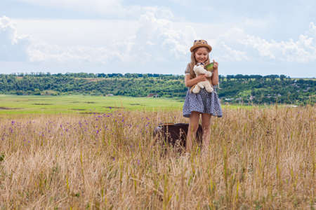 Child girl in a straw hat and dress sitting on vintage suitcase and drinking tea. Cute kid with soft dog toy looking at the cup in hands on nature lanscape background. Adventure concept in retro style