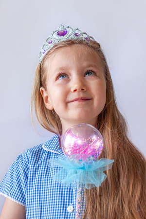 Beautiful little princess girl in silver crown holding sparkling magic wand and smiling. Young lady with long wavy hair in blue dress portrait on pastel light background.