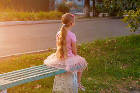 Cheerful little girl with long blonde hair in pink tulle skirt sitting alone on a bench on empty street on sunset. Happy dreamy cute child on nature background. Kids dress fashion. Greeting card.