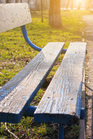 Old wooden park bench close-up on blurred green nature background. Relax backdrop for text sign, copy space banner with vertical orientation. Morning sun lights, calm tranquil wallpaper.