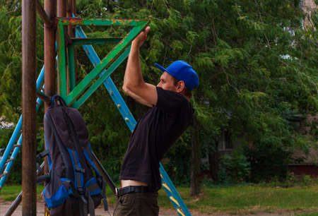 Athlete doing pull-up on horizontal bar. Male sportsman doing fitness exercises on playground outdoor during work break. Bearded young man with backpack warming up after working day. Active lifestyle. Фото со стока