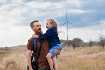 Father with daughter in hands standing on a hill with nature lanscape. Little blonde girl smiling and hugging with dad outdoor. Loving child embrace her daddy. Father's Day family greeting card.