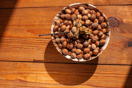 Hazelnuts in porcelain bowl on rustic wooden background. Raw fresh homegrowing nuts from house garden top view natural shadow. Organic dietary fiber, protein, vitamins source, healthy weight loss diet