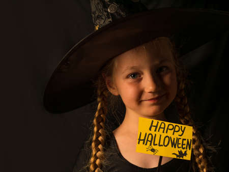 Little pretty girl witch in black wizard hat holds greeting Happy Halloween and laughs. Smiling positive child dressed in ghost party costume looking at camera. Festive autumn holiday wallpaper.