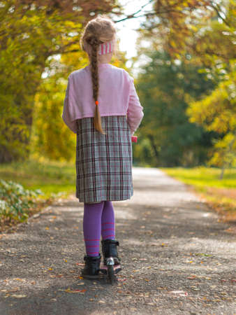 Child riding on kickscooter. Blonde cute girl in plaid dress on scooter on asphalt road. Autumn active lifestyle leisure, physical training on sports stadium. Happy childhood street photo with bokeh. Stock Photo