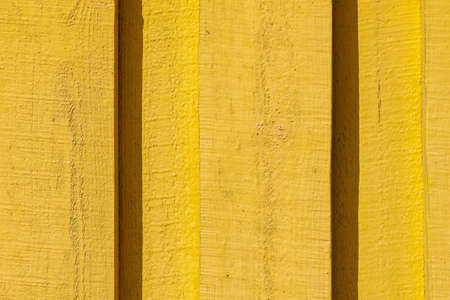 Yellow painted vertical planks wooden wall background. Creative wallpaper, website backdrop for design and text sign. Bright sunny color decorative texture. Close-up fence texture.
