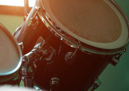 Black drum kit close-up. Musician set with mix of drums in studio. Musical instruments devices for drumming performance. Low key, dark and moody rock metal music style. Selective focus.
