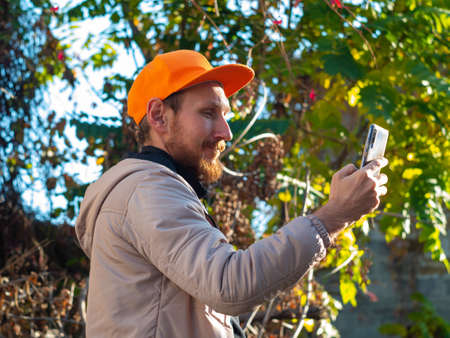 Young red bearded man speaks on mobile phone smiles. Guy in raincoat and orange cap on colorful autumn background. Positive emotional businessman answers smartphone call. Lifestyle work communication.