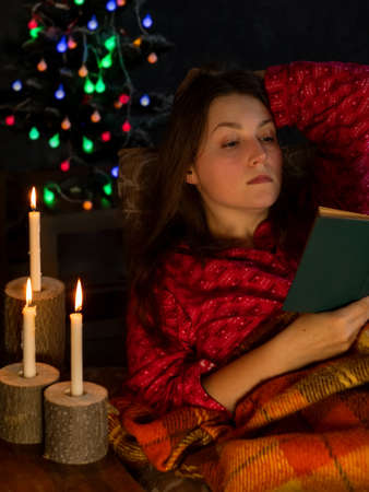 Young woman in a red pijama reads a book by the burning candles and glowing Christmas tree with festive decorations. Cozy vibes home comfort. Girl relaxing lying on sofa in lockdown. Stay home concept