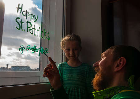 Drawing St. Patrick's Day Father with daughter painting green three-leaved shamrocks indoor, festive home decoration, family leisure. Drawing clover leaves on window glass. Stay home concept New normal