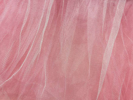 Pink tulle fabric texture top view. Coral background. Fashion rose color trendy feminine tutu skirt flat lay, female blog glossy backdrop for text sign design. Girly abstract wallpaper, textile surface