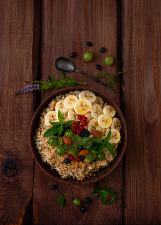 Wholegrain Oatmeal porridge bowl with fresh berries, fruits, nuts mint leaves flat lay. Healthy food oat meal morning breakfast top view. Whole grain cereal gooseberry currant banana on wooden table.