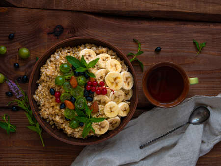 Wholegrain Oatmeal porridge bowl with fresh berries, fruits, nuts mint leaves tea cup. Healthy food oat meal morning breakfast top view. Whole grain cereal gooseberry currant banana on wooden table.