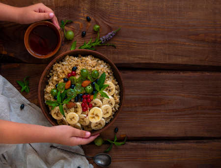 Wholegrain Oatmeal porridge bowl with fresh berry fruit nut mint leaves tea cup child hands. Healthy food oat meal morning breakfast top view. Whole grain cereal gooseberry currant banana wooden table