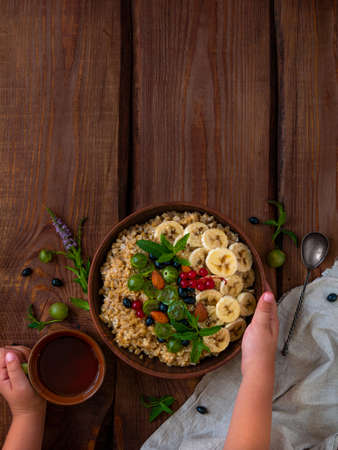 Wholegrain Oatmeal porridge bowl with fresh berry fruit nut mint leaves tea cup child hands. Healthy food oat meal morning breakfast top view. Whole grain cereal gooseberry currant banana wooden table 版權商用圖片