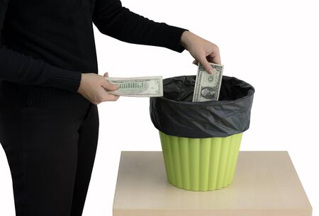 Money concept. Someone hand throwing money into the trash or green bin isolated on white background.