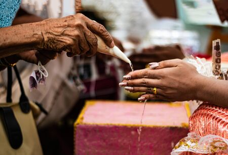 Elderly women pour the conch into their wedding hands. Asian wedding ceremony creating a shared future for men and women. Marriage makes the couple happy. Making life hopeful and peaceful in a married life.