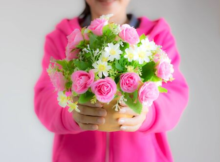 Girl wearing pink blurred image holding a bouquet of colorful flowers deliver to lover. Giving good feelings to each other pink flowers represent love and care. White represents purity. Stock Photo