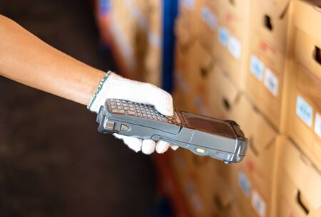 Staff wearing white gloves holding a barcode reader. the product has a sticker using modern technology to read values. Makes business and warehouse management convenient and easy.