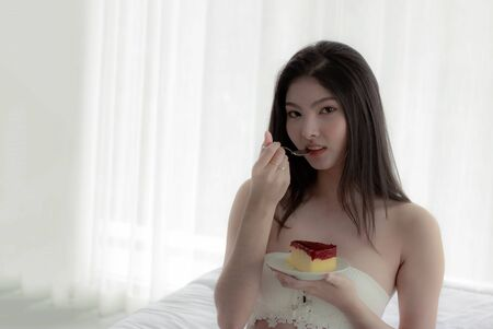 Beautiful Asian woman sit and relax in the bedroom. Happily having a snack on the bed. In the hands beautiful girl have a cake. Woman wearing white bra. Sitting and eating cake with deliciousness. Stock Photo
