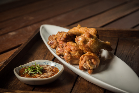 Fried chicken served with sauce made from tamarind sour on wooden tray