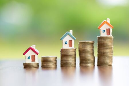 Saving money concept, coin stack growing business, save money for investment. coins to buy a home concept concept for property ladder. A small house on a pile of coins And have a financial chart. Фото со стока