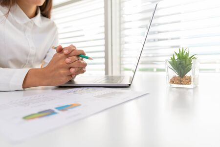 A business woman sitting on a desk with a laptop and graph with gestures in the office Concept .Take a break from the computer.And business planning project ideas for the future.