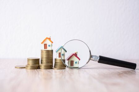 A magnifying glass that is being placed near the house on a pile of coins. Search for houses, investment ideas, real estate. Small houses have space to enter text.