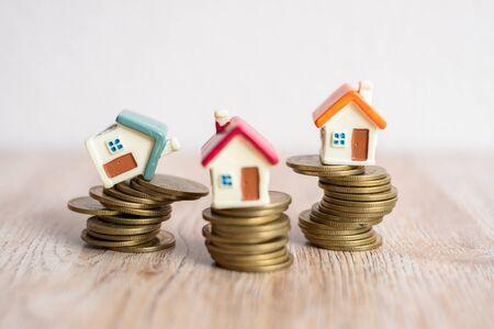 Mini huismodel en stapel munten. Huis op een munt die op het punt staat te vallen. Beheer van bedrijfsrisico's. Vastgoedinvestering en huishypotheek financieel onroerend goed concept.