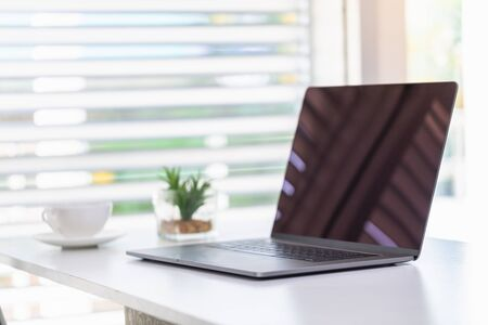 The laptop is placed on the work desk. Coffee cups and flowers are also placed.Working in the office. Business concepts, investors, accounting, clerks. A relaxed and convenient workplace.