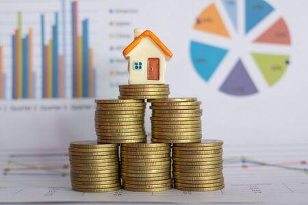 Ein kleines Haus auf einem Haufen Münzen und ein Finanzdiagramm. Mini-Hausmodell und Münzstapel. Geschäftswachstum. Immobilieninvestition und Haushypothek-Finanzimmobilienkonzept