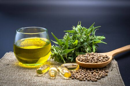 Hemp oil in a glass bottle Hemp seeds in a wooden spoon placed on the table. The concept of bringing hemp oil Extracted as a medicine By natural methods. The idea of planting seeds as seedlings. Reklamní fotografie